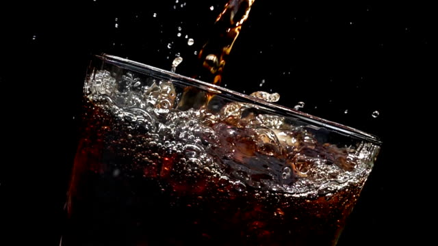 cola soda pouring into glass of ice with splashes at slow motion on a black background - pouring stock videos & royalty-free footage
