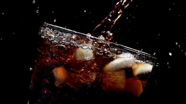 cola soda pouring into glass of ice with splashes at slow motion on a black background - refreshment stock videos & royalty-free footage