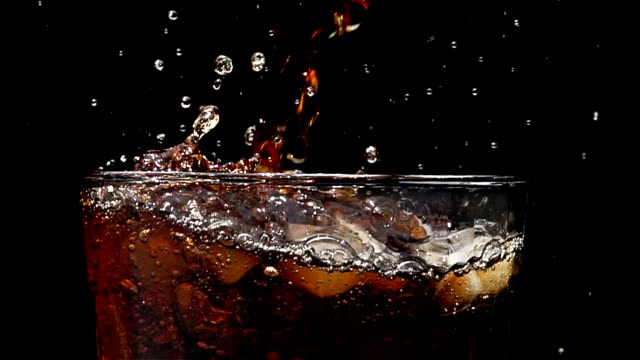 cola soda pouring into glass of ice with splashes at slow motion on a black background - carbonated drink stock videos & royalty-free footage