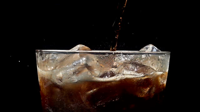 Pouring cola soda into glass of ice with splashes at slow motion on a black background