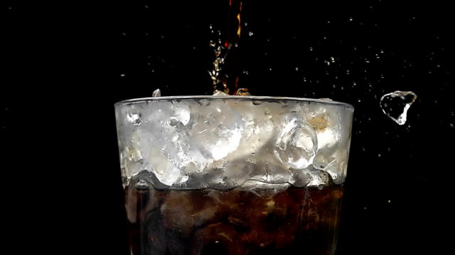 pouring cola soda into glass of ice with splashes at slow motion on a black background - splashing droplet stock videos and b-roll footage