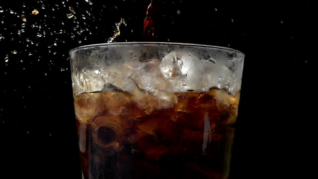 cola soda pouring into glass of ice with splashes at slow motion on a black background - cold drink stock videos and b-roll footage