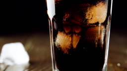 Cola with ice cubes and bubbles in glass, slow motion.