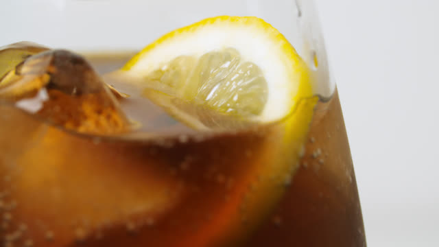 vidéos et rushes de cola with lemon and ice in glass - soda