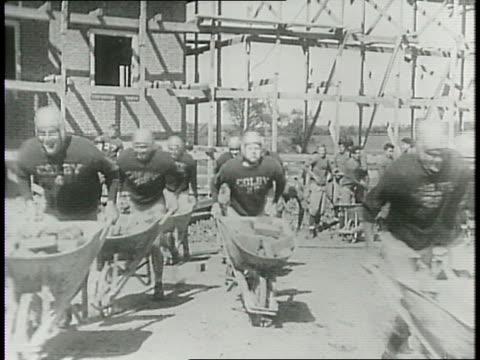 colby college football players in uniform charge towards the camera pushing wheelbarrows filled with bricks / montage of players climbing ladder up... - wheelbarrow stock videos and b-roll footage
