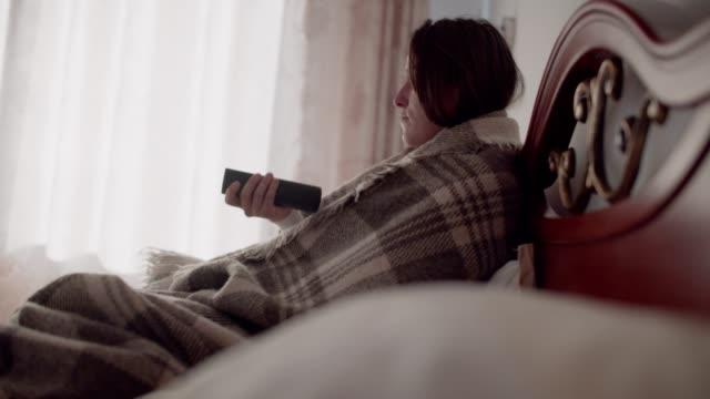 vidéos et rushes de froid et grippe. se reposer à la maison. belle jeune femme se trouvant dans le lit et regardant la tv. - douillet