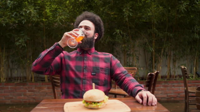 vídeos de stock e filmes b-roll de cold beer and tasty burger. what do you need more? - bigode