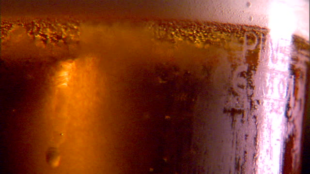 cu cold pint glass of draft beer being placed fg carbonation bubbles rising to small head glas moving back forward bitter pale ale lager pilsner... - pilsner stock videos & royalty-free footage