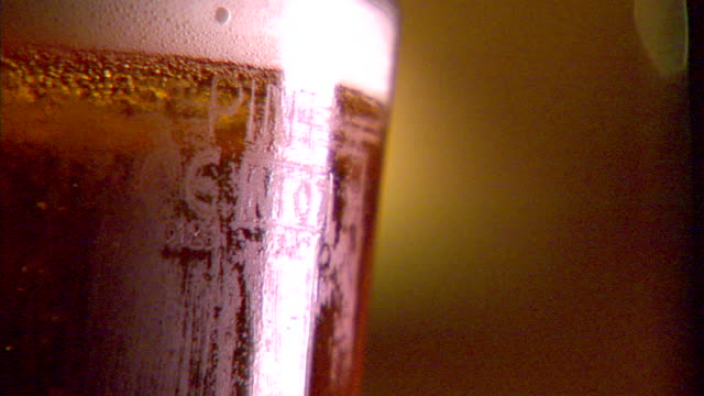 cu cold pint glass of draft beer pan glass cu carbonation bubbles in glassed draught beer bitter pale ale lager pilsner refreshing thirsty... - pilsner stock videos & royalty-free footage