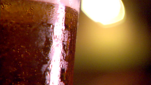 cu cold pint glass of draft beer turning carbonation bubbles rising bitter pale ale lager pilsner effervescence carbon dioxide gas bubbly refreshing... - pilsner stock videos & royalty-free footage