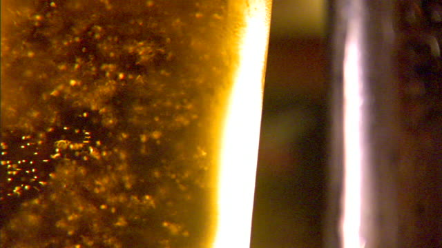 cold pint glass of draft beer w/ many carbonation bubbles rising topped w/ small head lager pale ale effervescence carbon dioxide gas yeast... - lager stock videos & royalty-free footage