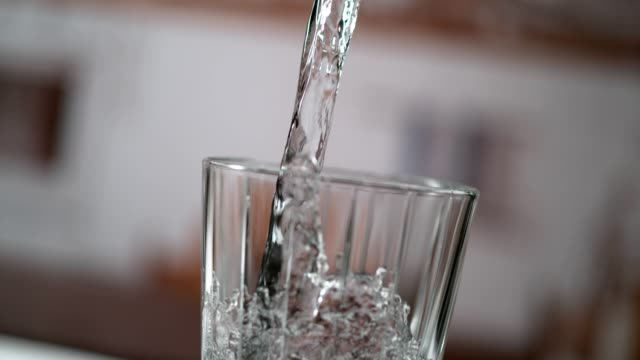 vídeos de stock e filmes b-roll de cold, purified water pouring into glass. super slow motion - copo