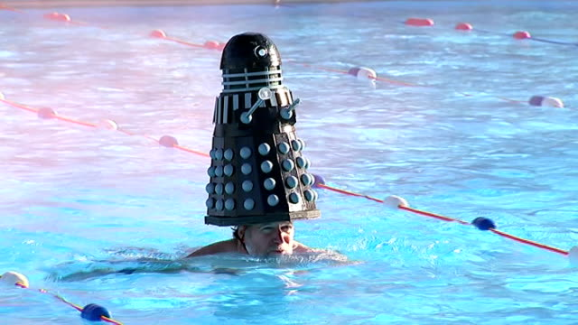 cold water swimming championships; england: london: tooting bec lido: ext swimmers along in pool woman swimming with dalek head gear swimmer... - drinking water stock videos & royalty-free footage