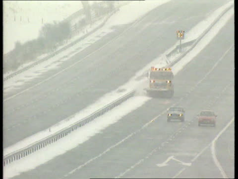 cold weather payments; itn yorkshire: m1 motorway: car along motorway thru falling snow, snowplough clearing outside lane of motorway with `50'... - road closed englisches verkehrsschild stock-videos und b-roll-filmmaterial
