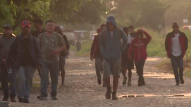 vídeos y material grabado en eventos de stock de colgados en trenes de carga o caminando por rutas boscosas y serpenteantes en la tiniebla nocturna decenas de migrantes indocumentados siguen... - ee.uu