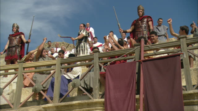 a coliseum crowd cheers for an archer during a reenactment of a roman blood spectacle. - historical reenactment stock videos & royalty-free footage