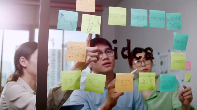 vidéos et rushes de idée de collaboration réflexion et stratégie dans le bureau du studio - étude de marché
