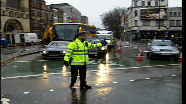 collapsed building on commercial road in whitechapel police officer directing pedestrian to cross road as traffic is held up behind him - anweisungen geben stock-videos und b-roll-filmmaterial