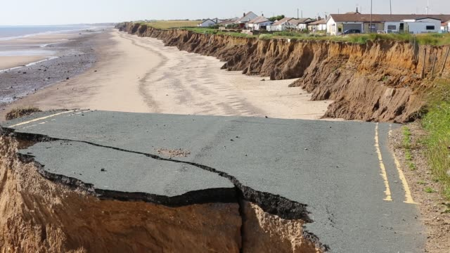 a collapsed coastal road at between skipsea and ulrome on yorkshires east coast, near skipsea, uk. the coast is composed of soft boulder clays, very vulnerable to coastal erosion. this sectiion of coast has been eroding since roman times, with many villag - coastal feature stock videos & royalty-free footage
