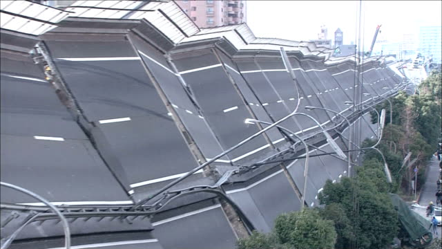 A collapsed highway bridge lies in ruins
