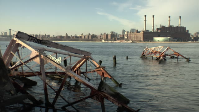 WS collapsed pier in the East River with view from Brooklyn of smokestacks and Lower Manhattan in background / New York City