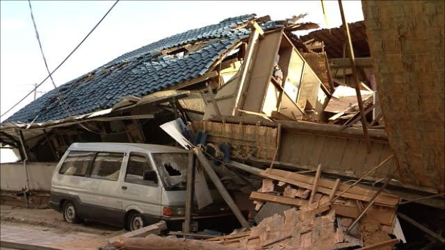 stockvideo's en b-roll-footage met collapsed wooden house and a passenger car underneath it medium shot - van