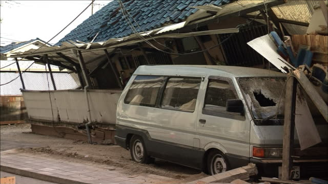 stockvideo's en b-roll-footage met collapsed wooden house and a passenger car underneath it medium shot zoom back collapsed house wide shot - van