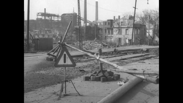 collapsed wroughtiron fence stands in front of debris and destroyed buildings in saarbrucken germany / collapsed railroad signs over train crossing... - 1945 stock-videos und b-roll-filmmaterial