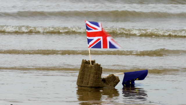 stockvideo's en b-roll-footage met collapsing sandcastle with eu and union flags - brexit