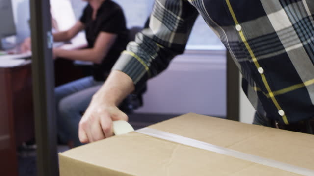 Colleagues at a business office working together, shipping boxes, and fulfilling orders