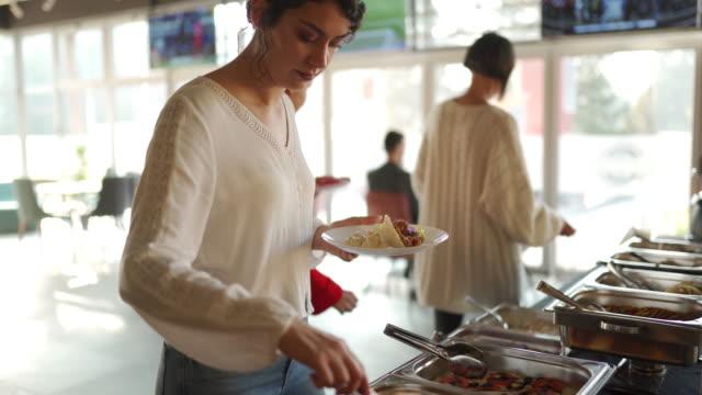 kollegen wählen essen am buffettisch im selbstbedienungsrestaurant - aussuchen stock-videos und b-roll-filmmaterial