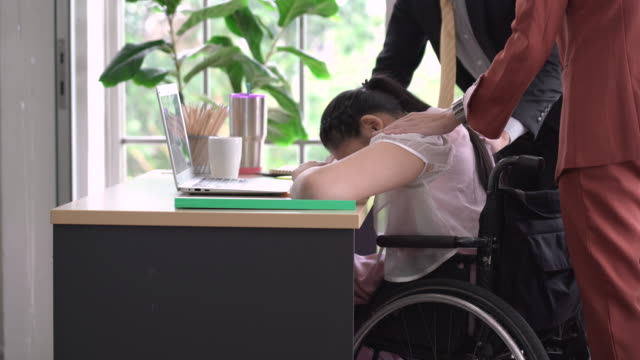 colleagues consoling sad woman sitting in wheelchair - comforting colleague stock videos & royalty-free footage