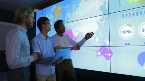 vídeos y material grabado en eventos de stock de compañeros debatiendo junto al muro de información interactiva - innovation
