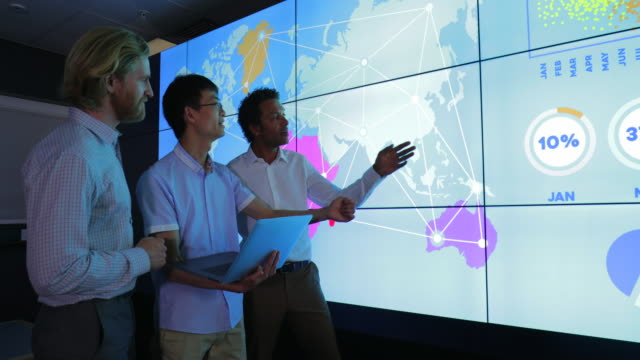 Colleagues Debating next to Interactive Information Wall