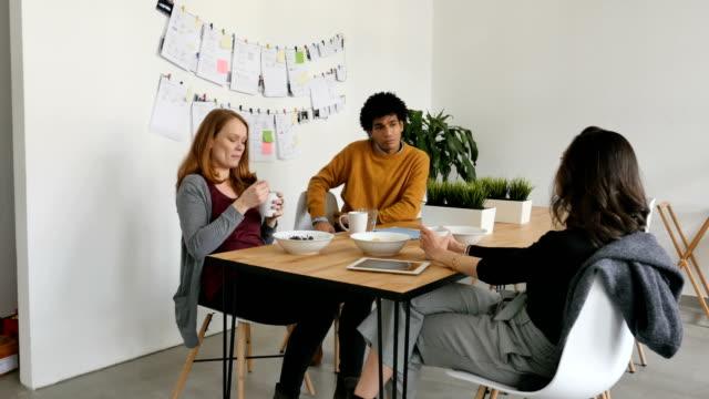 同事們在自助餐廳的餐桌上討論 - 休息 個影片檔及 b 捲影像