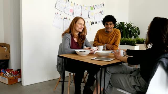 stockvideo's en b-roll-footage met collega's bespreken aan tafel in het cafetaria - kantine