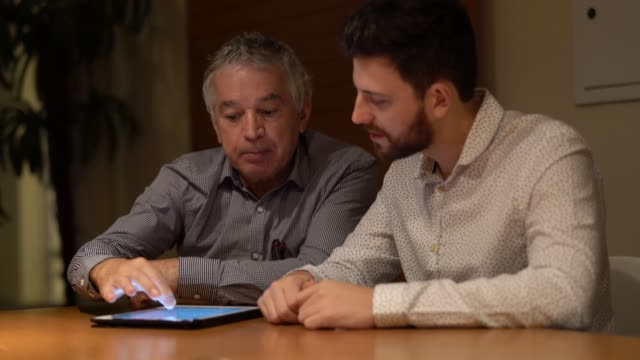 colleagues discussing new project using digital tablet at office - two people stock videos & royalty-free footage