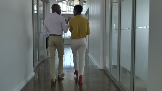 colleagues discussing while walking in corridor - office stock videos & royalty-free footage