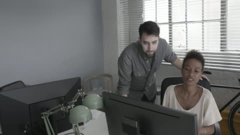 colleagues discussing work at computer - button down shirt stock videos & royalty-free footage