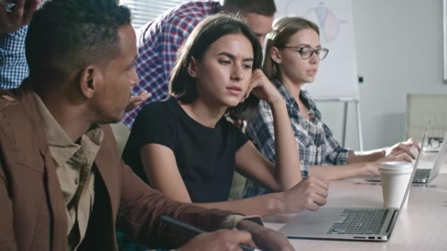 colleagues discussing work together in office - engångsmugg bildbanksvideor och videomaterial från bakom kulisserna