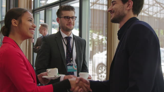 colleagues greeting each other during coffee break - business conference stock videos & royalty-free footage