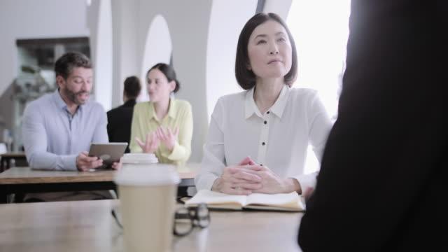 colleagues having a casual business meeting - カジュアルウェア点の映像素材/bロール