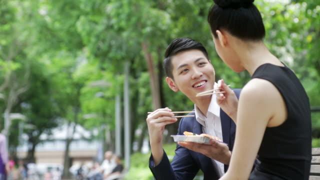 vídeos de stock e filmes b-roll de colegas ter pausa para almoço no parque - hora de almoço
