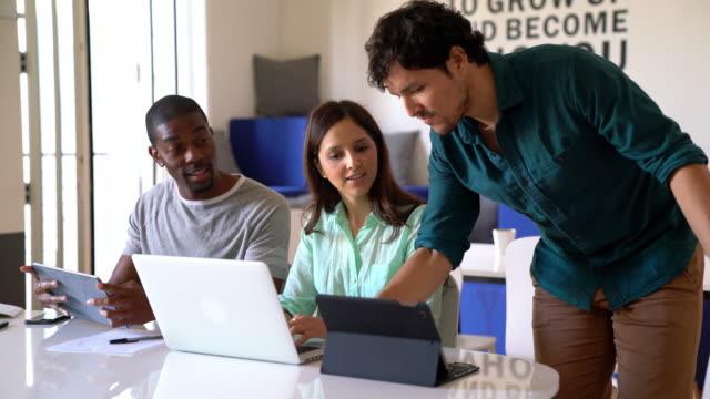 vídeos de stock, filmes e b-roll de colegas em um escritório moderno sentou-se a trabalhar quando um colega se junta a eles - três pessoas