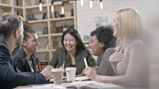 Colleagues laughing at funny joke at meeting