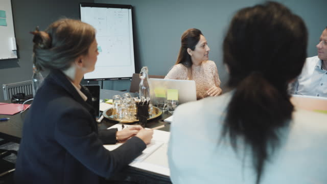 colleagues listening to confident businesswoman's sales pitch during meeting in board room at coworking office - sales pitch stock videos & royalty-free footage