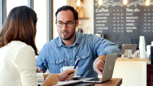 Colleagues meet at coffee shop to discuss business ideas