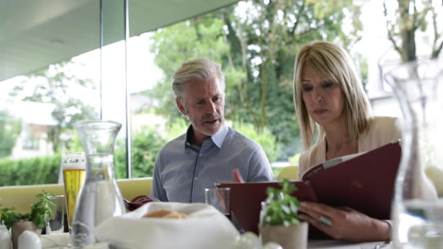 colleagues reading a menu in a restaurant - pensionierung stock-videos und b-roll-filmmaterial