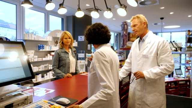 colleagues selling product to customer at pharmacy - receiving stock videos & royalty-free footage