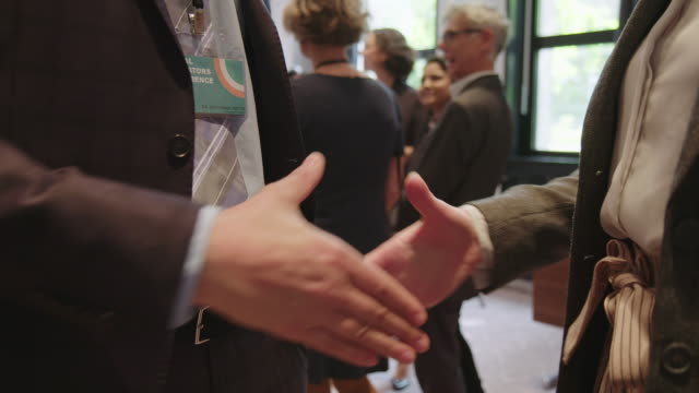 colleagues shaking hands in conference event - business relationship stock videos & royalty-free footage